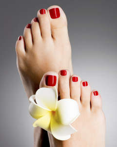 Closeup photo of a beautiful female feet with red pedicure and white flower