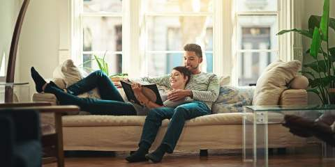 young couple laying on sofa reading in bright room